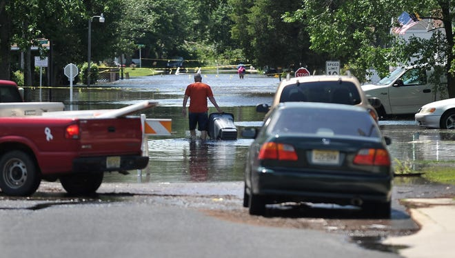 A man walks through a flooded section of Lakeside Boulevard, inside Cedar Crest Village mobile home park, Sunday, Jun. 28, 2015 in Vineland. Streams in the area were cresting and several roads were flooded Sunday after 4 inches of rain fell in Vineland on Saturday.
