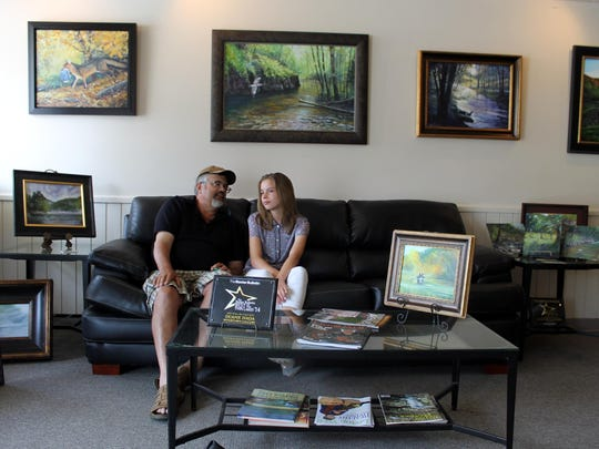Ava Obert sits with her mentor, Duane Hada, inside his Rivertown Gallery. She is the youngest artist to have her work represented by the gallery.