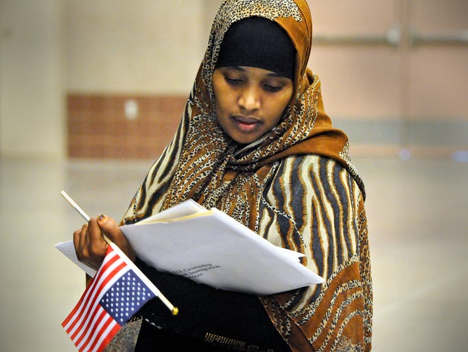 Hodan Mahad Adan looks at her Certificate of Naturalization following Wednesday's ceremony at the River's Edge Convention Center in St. Cloud. 84 people from 34 countries became citizens during the ceremony.