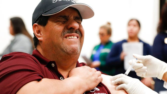 Cesar Gonzalez reacts to getting an influenza vaccine shot at Eastfield College in Mesquite, Texas. The CDC estimates there have been between 180,000-310,000 hospitalizations and 10,000-25,000 deaths from the flu in the United States this flu season.