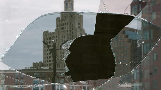 The Providence skyline is reflected in a broken window of the Capitol Cove building on June 2, after rioting and looting took place overnight.