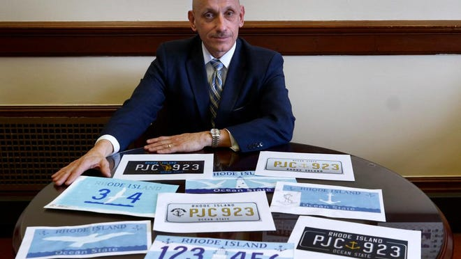 Sen. Louis DiPalma is photographed with printouts of Rhode Island license plate designs that have been submitted but the project to replace the plates has been put off until December, at the earliest.