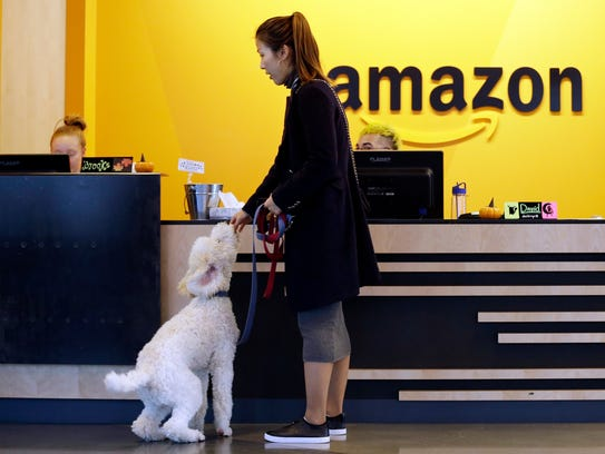 An Amazon employee gives her dog a biscuit as the pair