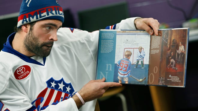 """Amerks player Nick Petrecki, who was sitting next to teammate Jake McCabe, reads """"Z is for Zamboni"""" for a Family Reading, putting the protective gear on one of the kids and giving away sticks at the Boys and Girls Club in Rochester."""