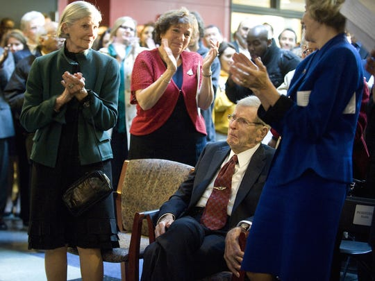 A crowd, including wife Lee Rowan (left) and daughter Virginia Rowan Smith (right), rise to applaud Rowan University benefactor Henry Rowan during a statue dedication ceremony in 2012.