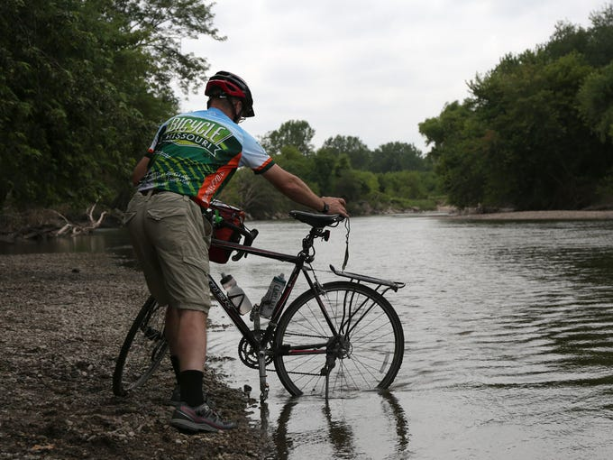 Jon Harman of Marthasville, Missouri, dips his back tire into the Rock River during RAGBRAI on Saturday, July 19, 2014, in Rock Valley, Iowa.