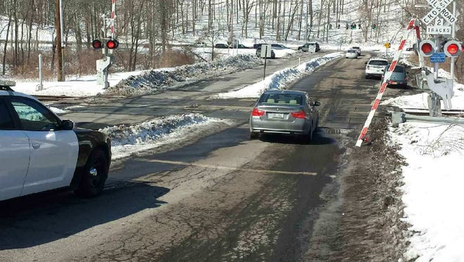 The Roaring Brook Road rail crossing is shown with a broken gate after an earlier accident, in March. The intersection's troubles continued Monday, local police said, when a school bus that had pulled too far forward was clipped by a lowering crossing gate.