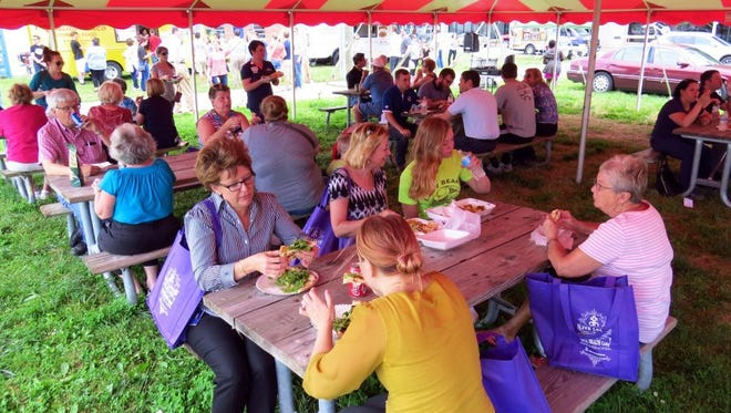 Diners enjoy lunch under the pavilion at the Farmers Market in Evansville.