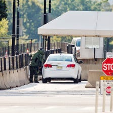 An explosive technician in a bomb suit approaches a vehicle near the entrance to White House on Saturday. Secret Service says a man has been arrested for trying to unlawfully enter the White House, less than 24 hours after a fence-jumper made it all the way into the building.