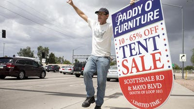 Butch Franklin works traffic with a sale-touting sign on May 15 at Loop 101 and Shea Boulevard in Scottsdale.