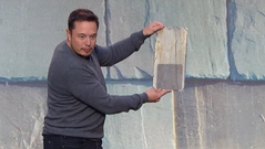 Tesla CEO Elon Musk shows a Tesla solar roof cell.