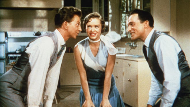 "Donald O'Connor as Cosmo Brown, Debbie Reynolds as Kathy Selden, and Gene Kelly as Don Lockwood in ""Singin' in the Rain."""