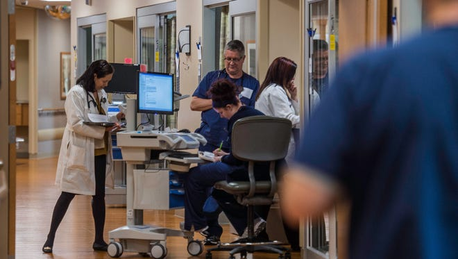 Doctors and nurses interact in a hallway in the Reid Health critical care area on Wednesday, Sept. 27, 2017.