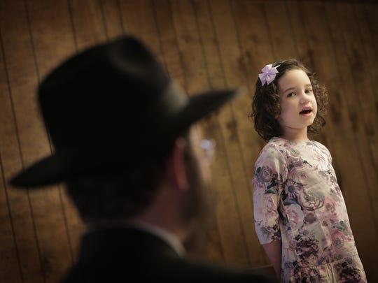 Rabbi Levi Greenberg listens as his daughter, Musia,