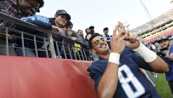 Quarterback Marcus Mariota  takes a selfie with fans