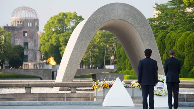 Japanese Prime Minister Shinzo Abe looks on as President Obama lays a wreath during a visit to the Hiroshima Peace Memorial Park on Friday.