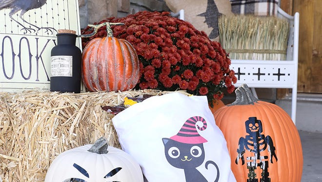 Hay bales and chairs can be used as a place to set fall-themed decor at varying levels.