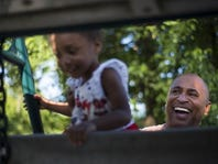 Jonathan White laughs as he helps his soon-to-be-adopted daughter Courtney, 2, up a ladder at the park on June 9.