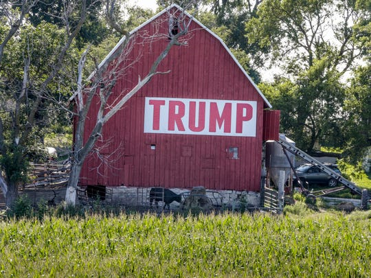 A field of corn is seen in front of a barn carrying a large Trump sign in rural Ashland, Neb., Tuesday, July 24, 2018. The Trump administration announced Tuesday it will provide $12 billion in emergency relief to ease the pain of American farmers slammed by President Donald Trump's escalating trade disputes with China and other countries. (AP Photo/Nati Harnik)