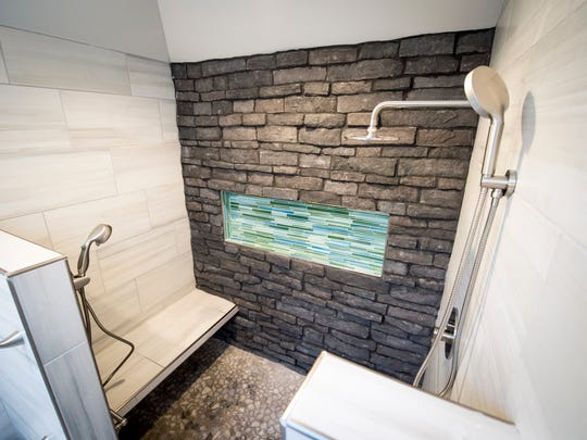 The renovated bathroom, which features a seated shower,