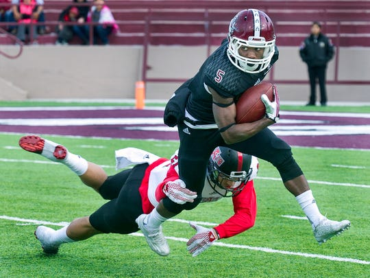 New Mexico State receiver Tyrain Taylor hauls in a pass and breaks the shoestring tackle of Arkansas State's Cody Brown during second quarter action on Saturday afternoon at Aggie Memorial Stadium.