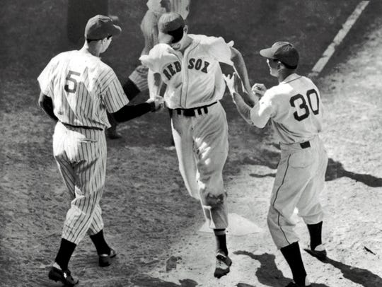 Ted Williams, center, is greeted at home plate by teammate