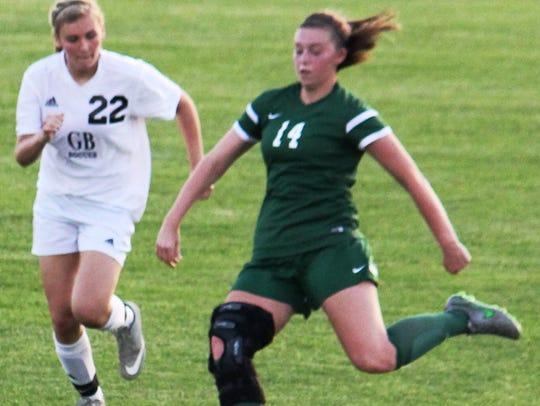 Novi's Megan Riley (14) moves the ball ahead of Grand