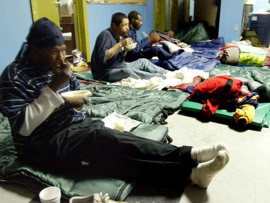 In this Dec. 10, 2008, file photo, homeless people are provided a warm meal and place to spend the night at a Lafayette shelter.