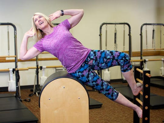 Leah Sine, owner of Pilates Edge USA, executes a pilates exercise called a side lift.