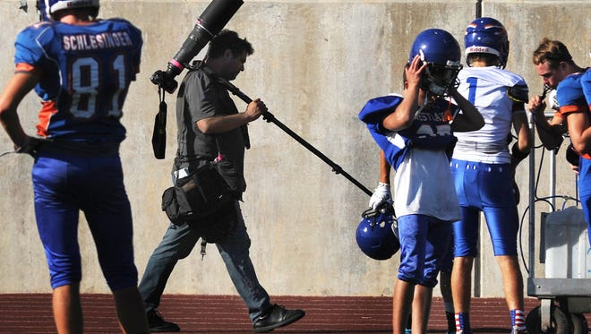 On assignment at a Westlake High School football practice staff photographer Joseph Garcia, also on assignment, worked on the opposite side of the field. Keeping a watchful eye I made a few photos as he appeared between several players as the ace photographer moved to another vantage point.