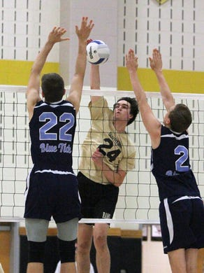 2015 NJSIAA Boys Volleyball state semifinals held at South Brunswick High School on Tuesday June 2, 2015. Southern Regional vs Harrison in the first semi final.Southern's # 24 (center)- Liam Maxwell gets the ball between two Harrison defenders during the 1st game.