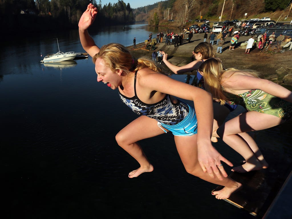Heidi Edgecombe, left, gives a yell as she makes the jump from the bridge with Savannah Easterday and Nancy Martin at the annual Olalla Polar Bear Plunge in Olalla, Wash.