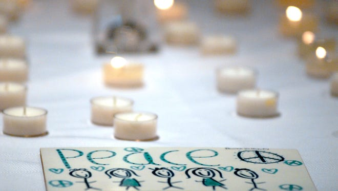 Guest were encouraged to light a candle for peace at Interfaith Paths to Peace interfaith solidarity and prayer vigil for peace at Christ Church Cathedral.  The vigil is a response to the terrorist attacks on Belgium Tuesday.  March 23, 2016