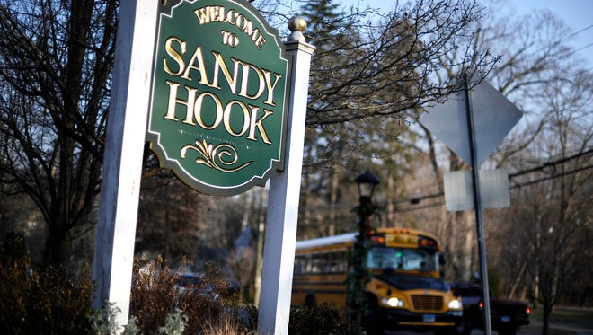 """A bus drives past a sign reading """"Welcome to Sandy Hook"""" on Wednesday in Newtown, Conn."""