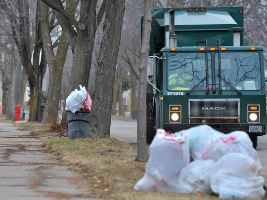 City staff collects garbage Monday afternoon, March 16, 2015, on North Tenth Avenue in Wausau.