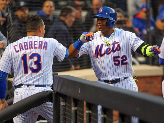 Mets outfielder Yoenis Cespedes (52) celebrates in the dugout with teammate Asdrubal Cabrera after hitting a two-run home run during the first inning against the Atlanta Braves on May 2. The New York Mets are one of several sports teams that use dynamic pricing software to raise or lower prices depending on weather, opponents and many other factors.