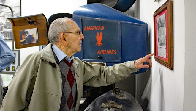 George Washington Whitehouse examines a photograph from the earlier days of the Millville Army Air Field.