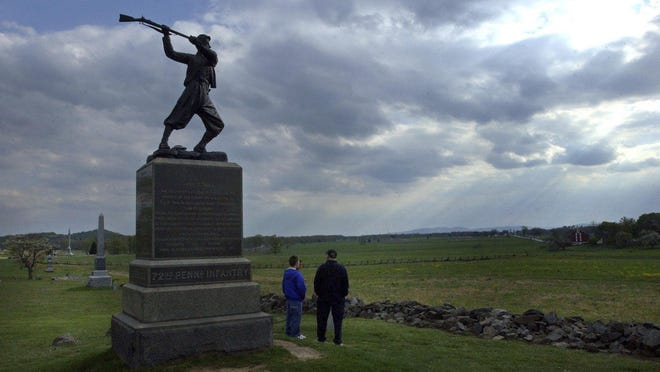 Tourists look out over historic Gettysburg battlefields near a statue honoring the 72nd Pennsylvania Infantry in Gettysburg National Military Park in Gettysburg, Pa.