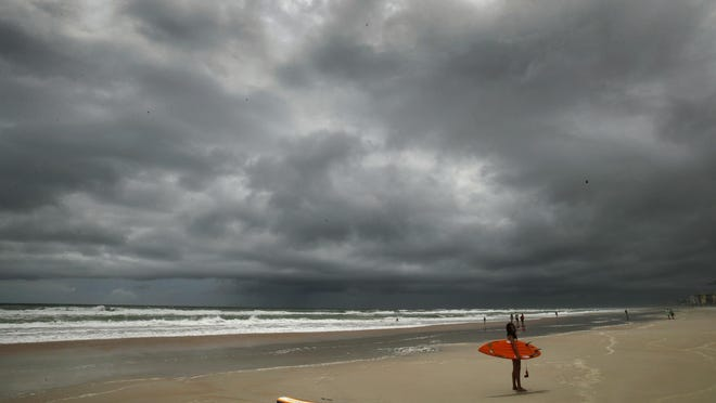 A surfer prepares to challenge the waves under stormy skies of Tropical Storm Isaias on  Sunday.