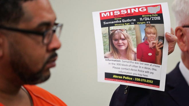 William Alexander looks at a missing poster of Samantha Guthrie, an Akron woman killed in November 2018, during his sentencing in October 2019.