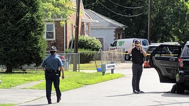 A state police trooper walks near the scene of the incident on Tuttle Street in Saugus, Aug. 6, 2020.