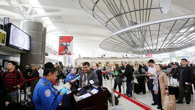In this photo taken Oct. 30, 2014, a TSA officer, left, checks a passenger's ticket, boarding pass and passport as part of security screening at John F. Kennedy International Airport in New York.