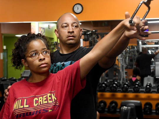Rodney Stephenson shows his 15-year-old daughter Eliese proper form to exercise her shoulders during a morning training session at Anytime Fitness, Tuesday, June 12. Eliese says she enjoys exercising with her dad because it allows her and her two sisters to spend time with him.