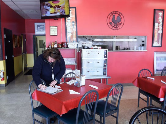 Food inspector Ivonne Rodriguez writes notes about