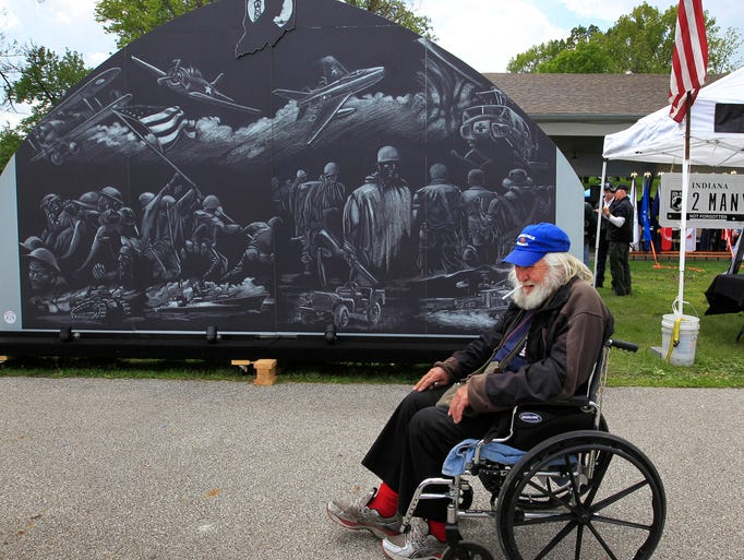 Homer Massey, 74, a Georgia resident staying in Indianapolis for knee surgery at the veterans hospital, rolls past the Rolling Thunder Indiana Chapter One's POW-MIA tribute mural on display at the 4th Annual Mayor's Veterans Family Appreciation Day picnic and fish fry at Garfield Park on Saturday, May 17, 2014. Massey served in the National Guard, then the U.S. Air Force for eight years and finally as a contractor for the U.S. Navy. The mural, depicting wars from World War I to the present, was conceived by the Lafayette Chapter of Rolling thunder, then finished by Chapter One.