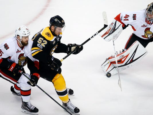 Boston Bruins' Sean Kuraly (52) and Ottawa Senators' Zack Smith battle for the puck in front of Ottawa goalie Craig Anderson (41) during the third period in game six of a first-round NHL hockey Stanley Cup playoff series, Sunday, April 23, 2017, in Boston. The Senators won 3-2. (AP Photo/Michael Dwyer)