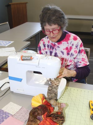 Lois Miller adjusts her fabric as she assembles a piece of a quilt during a quilting day Tuesday, Nov. 7, at the Williamsburg Public Library.
