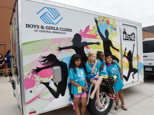 Boys & Girls Club members pose for a photograph with the Move Mobile - Activity on the Go project trailer before a ceremony Tuesday, July 25, at the Roosevelt Boys & Girls Club in St Cloud.