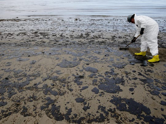 A worker removes oil from the beach at Refugio State Beach, north of Goleta, Calif., Thursday. More than 7,700 gallons of oil has been raked, skimmed and vacuumed from a spill that stretched across 9 miles of California coast, just a fraction of the sticky, stinking goo.