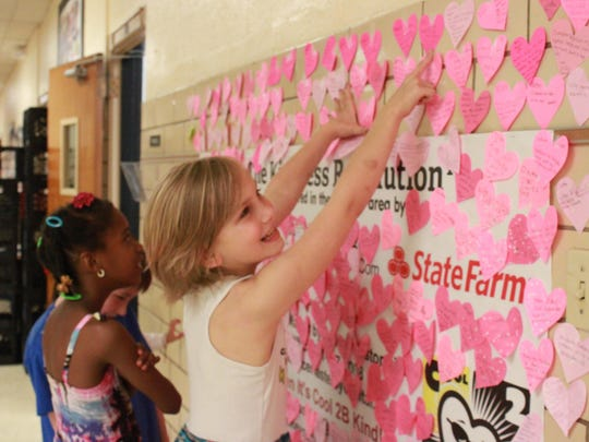 Maggie Painter, 9, points to a heart recording a kind action Wednesday at Alexander Elementary School.